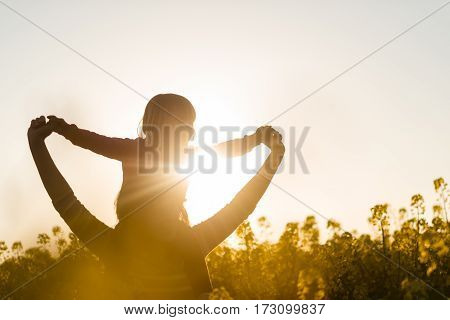 Girl child sits on shoulders of mother, facing towards sun.