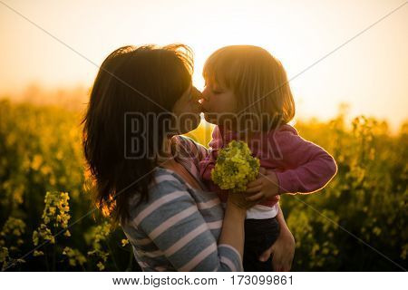 Young mother and her little girl kissing each other at a sunset scene