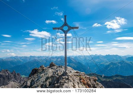 Summit marker on Krottenkopf, Austria with an overview of distant alpine mountain ranges on a sunny blue sky summer day in a concept of sporting achievement