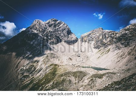 Bare mountain peak in Austria under shadows of scattered clouds in blue sky and copy space above