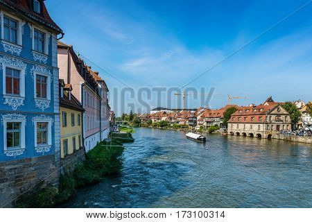 Medieval German village Bamberg on both sides of river Regnitz as tourist boat travels nearby