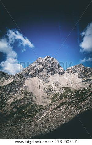 Low angle view on bare rocky mountain under deep blue sky with scattered clouds. Includes copy space.