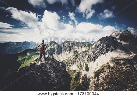Mountain climber wearing a backpack standing on a rocky summit of an alpine peak looking out over the view of high alps and forested valleys on a cloudy blue sky day with vignette