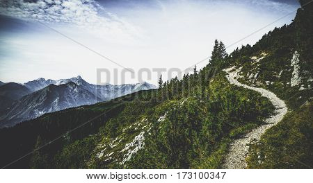 Hiking trail through forested alpine peaks in summer sunshine with a view of distant summits and ranges in a scenic Austrian landscape