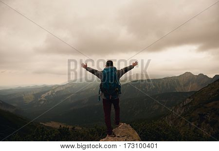 Rearview of a man in hiking gear with arms raised to the sky embracing the view from a mountain peak while trekking in the wilderness
