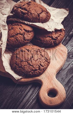 chocolate cookies with chocolate on the black wooden background