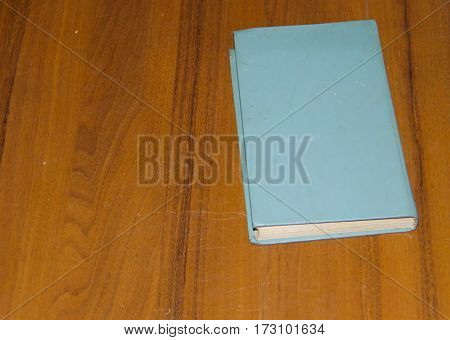 Old closed book on the wooden table