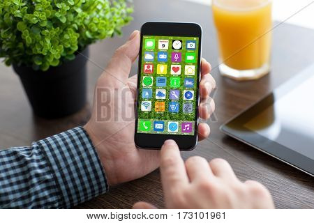 man hands holding phone with home screen icons apps in office