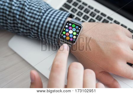 Man hands and smart touch watch with home screen icons apps background laptop