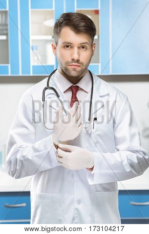 portrait of serious doctor in medical uniform and gloves in lab