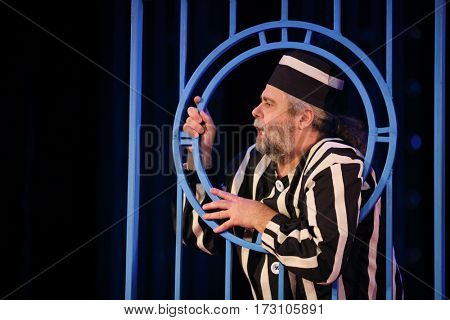 MOSCOW - OCT 19, 2016: Actor prisoner behind lattice during Premium class Performance in Modern theater