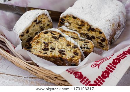 German Christmas stollen cut into slices powdered in wicker basket with knife kitchen towel top view close up