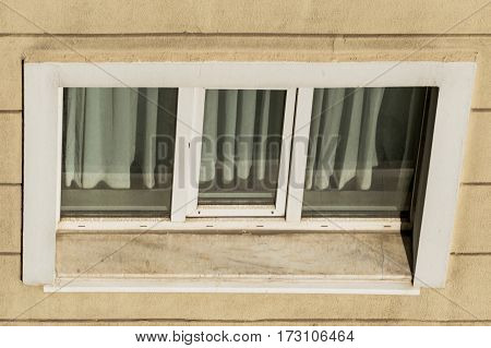 High angle view of an apartment window with closed curtains
