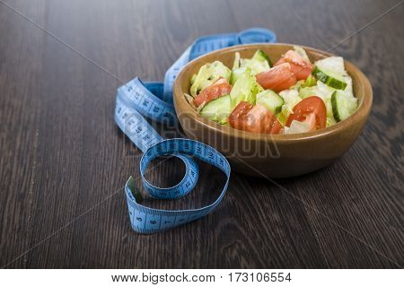 Salad In Wooden Bowl And Measuring Tape On A Table Close-up.