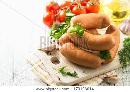 Uncooked sausages with herbs and vegetables on white wooden table.