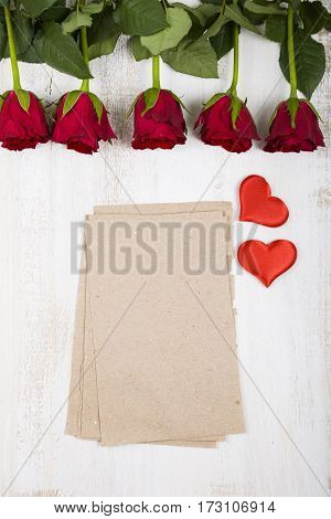Red Roses And Paper For Congratulations On A Wooden Background.