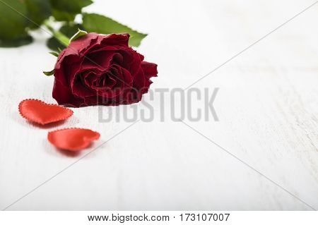 Red rose and heart on a wooden background. Greeting card with Valentine's Day Birthday or Wedding.