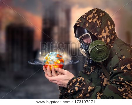 Man in gas mask looking at a globe in his hands. The planet glows continents in flames. A man in uniform