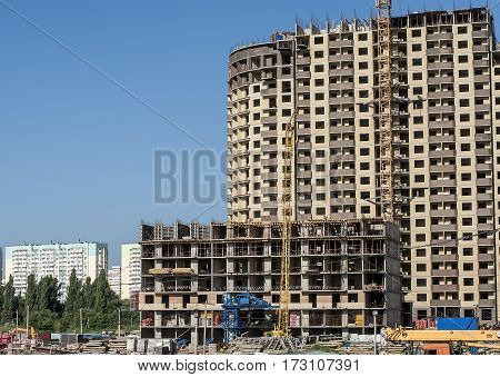High-rise residential buildings in various stages of construction on the background of the neighborhood