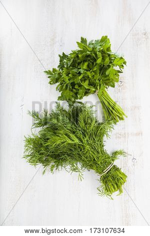 Parsley And Dill On A Light Wooden Background.