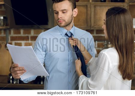 businessman reading documents while wife tying tie