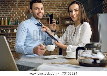 businesswoman helping husband tying tie during breakfast