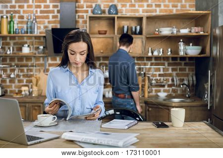 Attractive young businesswoman reading magazine while working at home