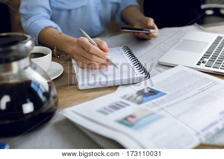Close-up partial view of woman taking notes while using smartphone