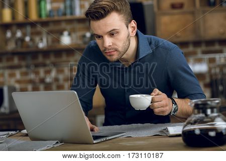 Concentrated young man using laptop while drinking coffee at home