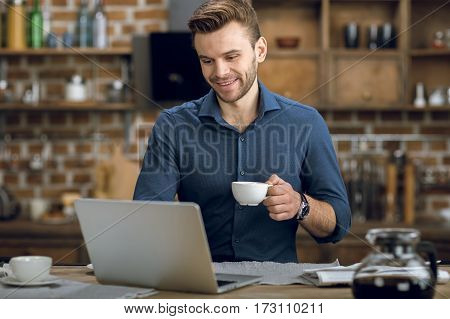 Smiling young man using laptop while drinking coffee at home