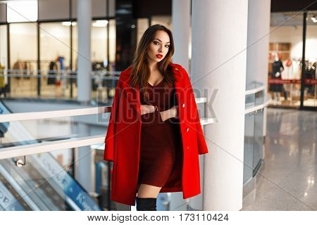 Fashionable Beautiful Young Woman In A Red Coat In A Shopping Center