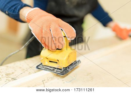 Closeup Of Woman Using A Sander