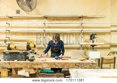 Measuring Some Wood In A Workshop