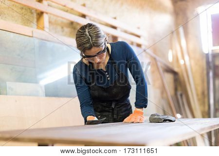 Carpenter Using Sand Paper On A Wooden Table
