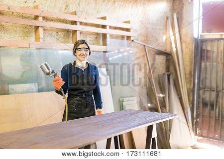 Cute Female Carpenter Using Spray Gun