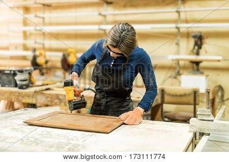 Woman Using Nail Gun In A Woodshop