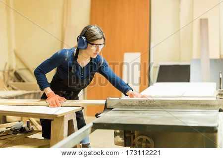 Woman Using Table Saw In A Woodshop