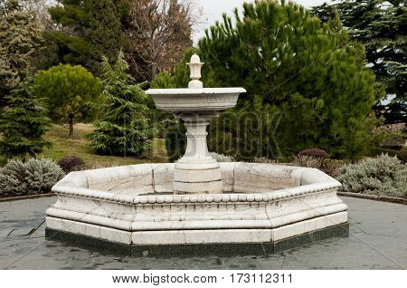 stone old fountain without water in the park