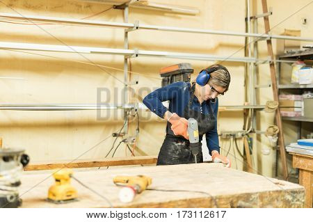 Good looking young woman working in a woodshop and using a screwdriver poster