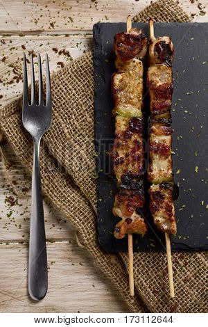 high-angle shot of some barbecued spiced chicken meat skewers on a slate tray, placed on a rustic wooden table