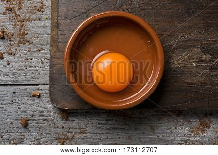 high-angle shot of an earthenware plate with a cracked chicken egg on a rustic wooden table