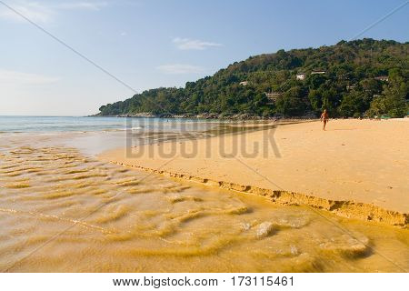 Phuket Thailand January 29 2017: The river flows through the yellow sand and empties into the ocean.
