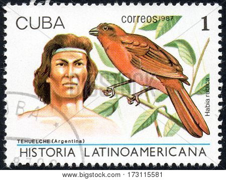 UKRAINE - CIRCA 2017: A stamp printed in Cuba shows a native of Argentina Tehuelche and bird Habia rubica the series Latin American history circa 1987