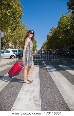 brown hair adult woman with grey dress and sunglasses in summer walking with red suitcase on crosswalk in Madrid urban street