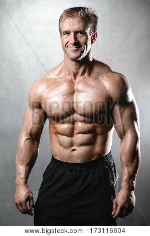 Brutal Strong Bodybuilder Old Man Posing In Studio Grey Background