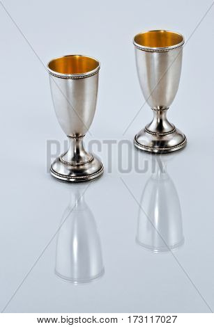 On a white background - two silver cups gilded inside. Retro noble form.