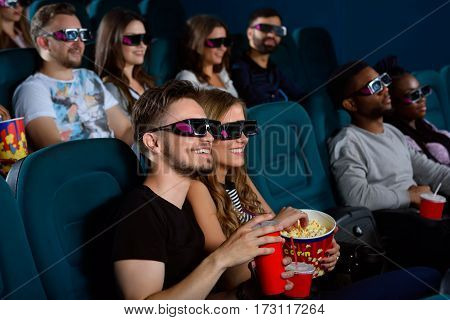 Checking out a new blockbuster. Shot of a happy young couple having a date at the cinema watching a 3D movie together smiling cheerfully