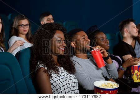 Enjoying a great movie with closest ones. Portrait of a group of young friends smiling while watching a movie at the cinema together