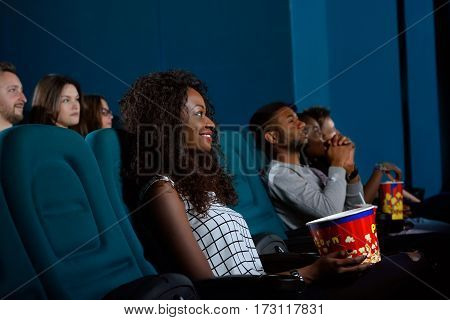No better thing than a movie. Shot of an attractive young African woman smiling as she is looking at the cinema screen with interest enjoying a movie
