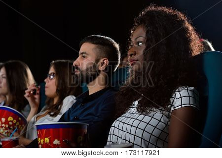 Chilling with friends. Low angle shot of a beautiful African woman watching a movie with her friends at the local movie theatre